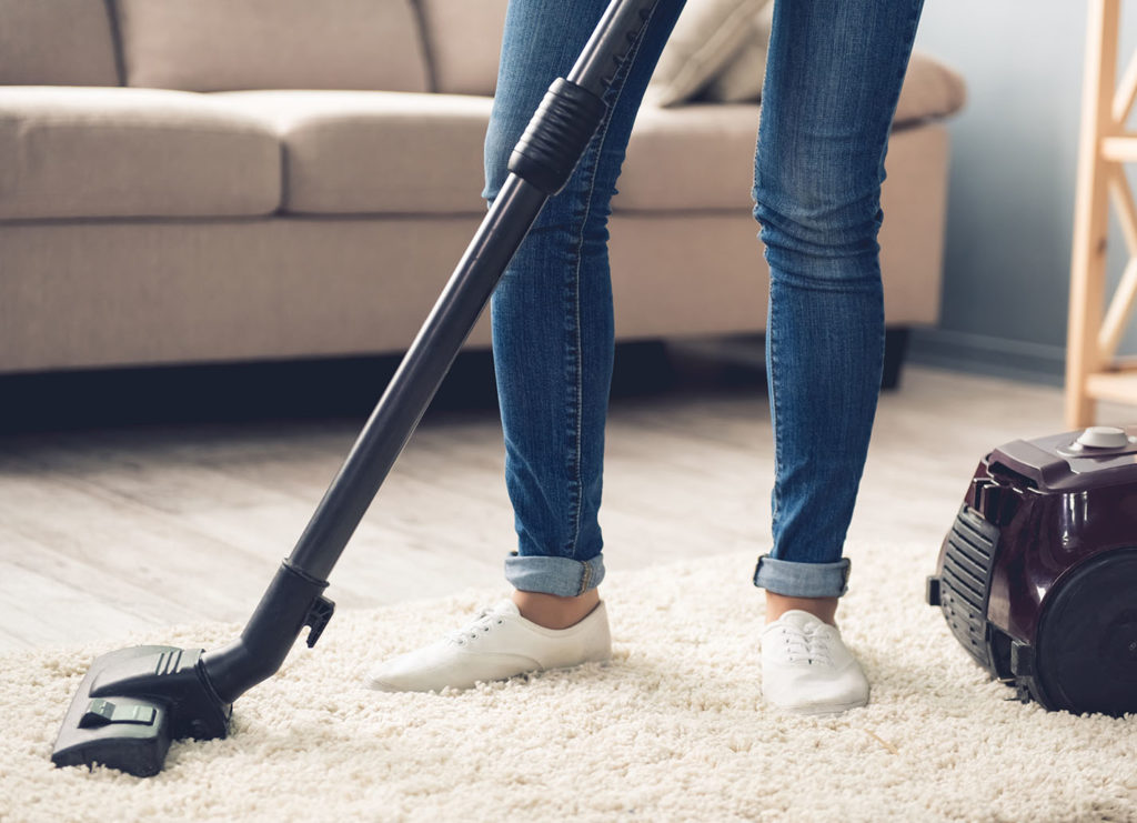 a woman vacuuming a white rug