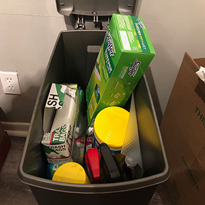 garbage can filled with cleaning supplies