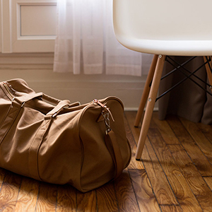 brown duffel bag sitting on the floor next to a white chair