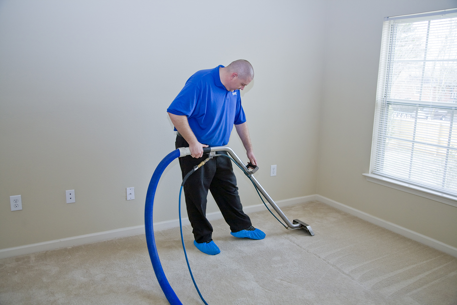 carpet cleaner cleaning a tan carpet