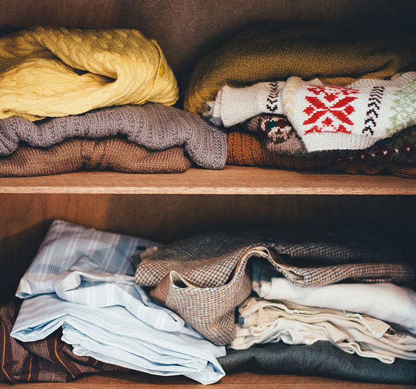 clothes stacked on a closet shelf
