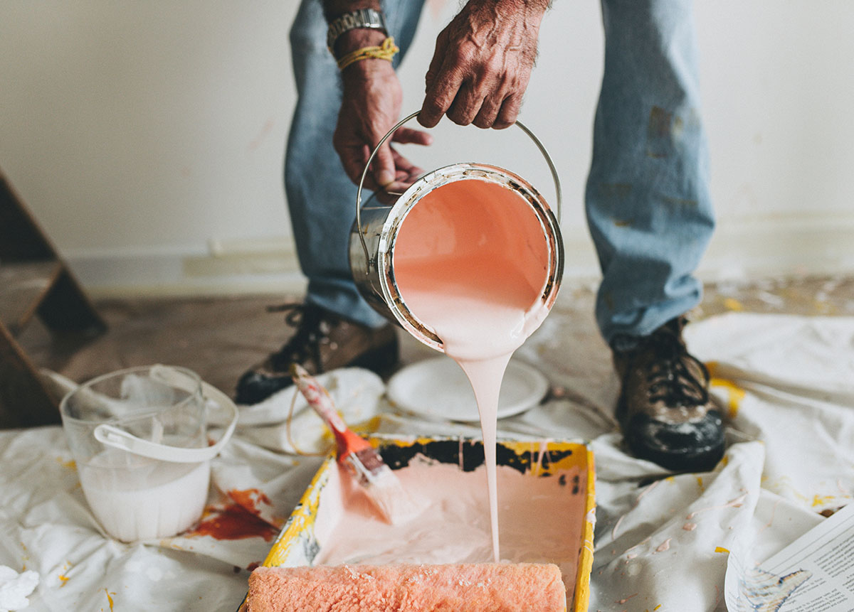 man pouring pink paint into a pan