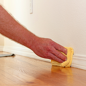 person cleaning baseboards with a yellow rag