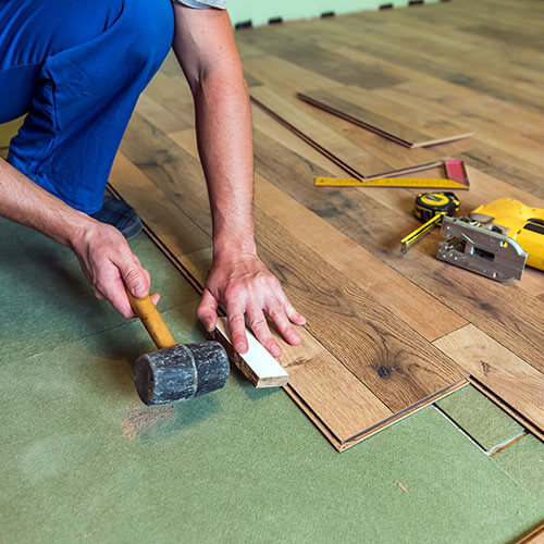 man with a mallet installing flooring