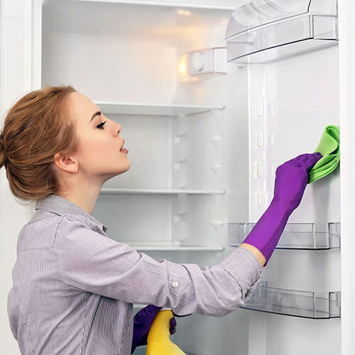 woman cleaning a refrigerator