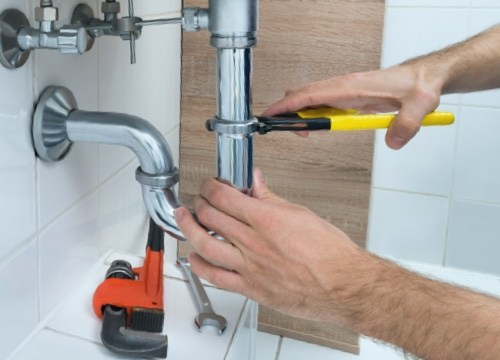 man repairing a sink pipe