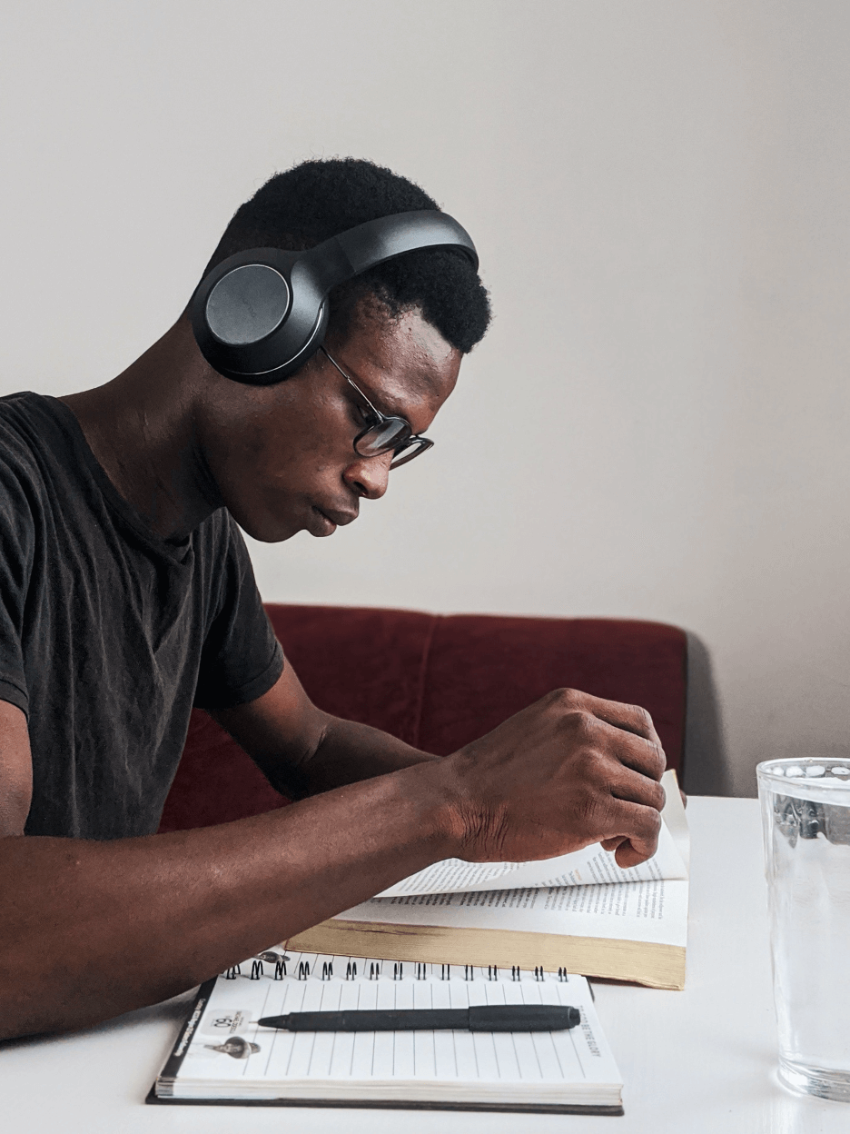 university student with headphones on reading a book